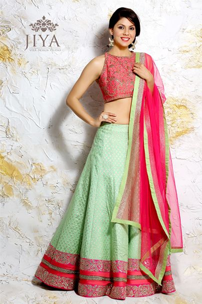 Fresh colors of mint on an elegant chanderi lite lehenga, perfect for summer glam. The hem is done up with panels of pretty rose pink with gota patti work. The stylish incut racerback choli in pink is embellished with zardosi. The style comes with a matching dupatta.
