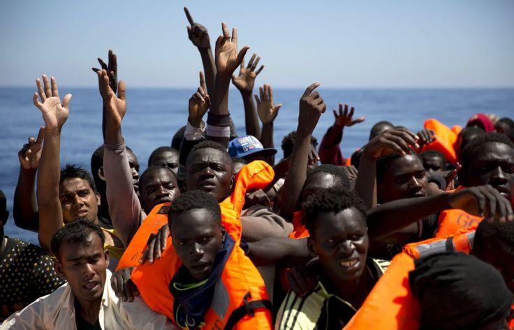 Migrantes y refugiados levantan la mano mientras tratan de alcanzar los chalecos salvavidas distribuidos por la ONG española Proactiva Open Arms, tras ser localizados navegando en el mar Mediterráneo sin rumbo, a unos 18 kilómetros al norte de Sabratha.