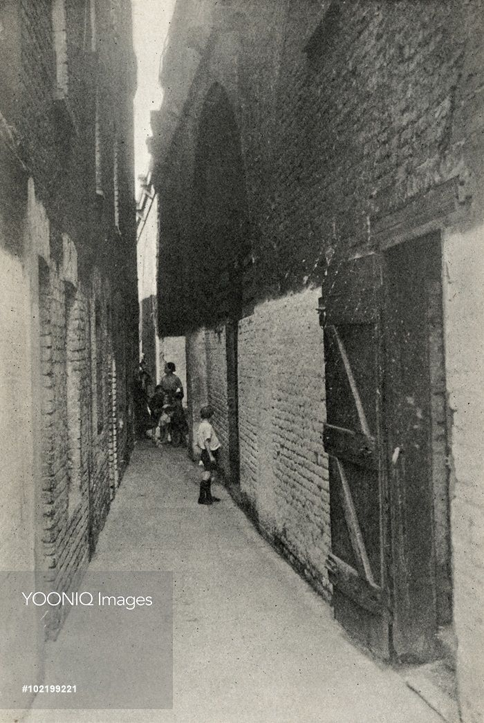 Yooniq images - Women and children in a passageway between blocks of poor housing in the Shadwell district of Stepney in London's East End.
