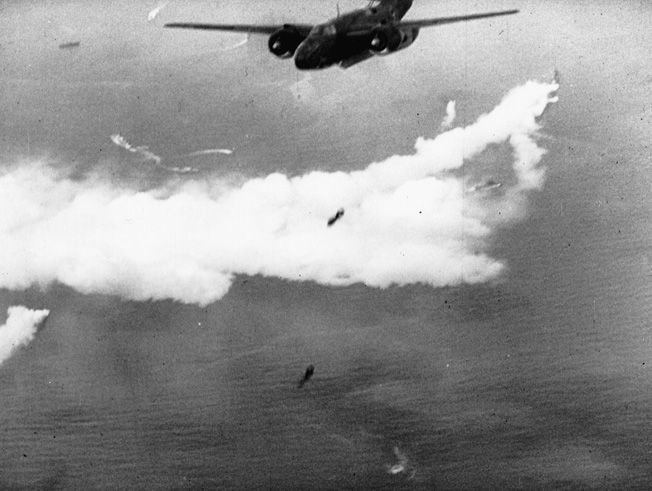 As British naval units lay a smokescreen far below, RAF bombers release their payload over Dieppe