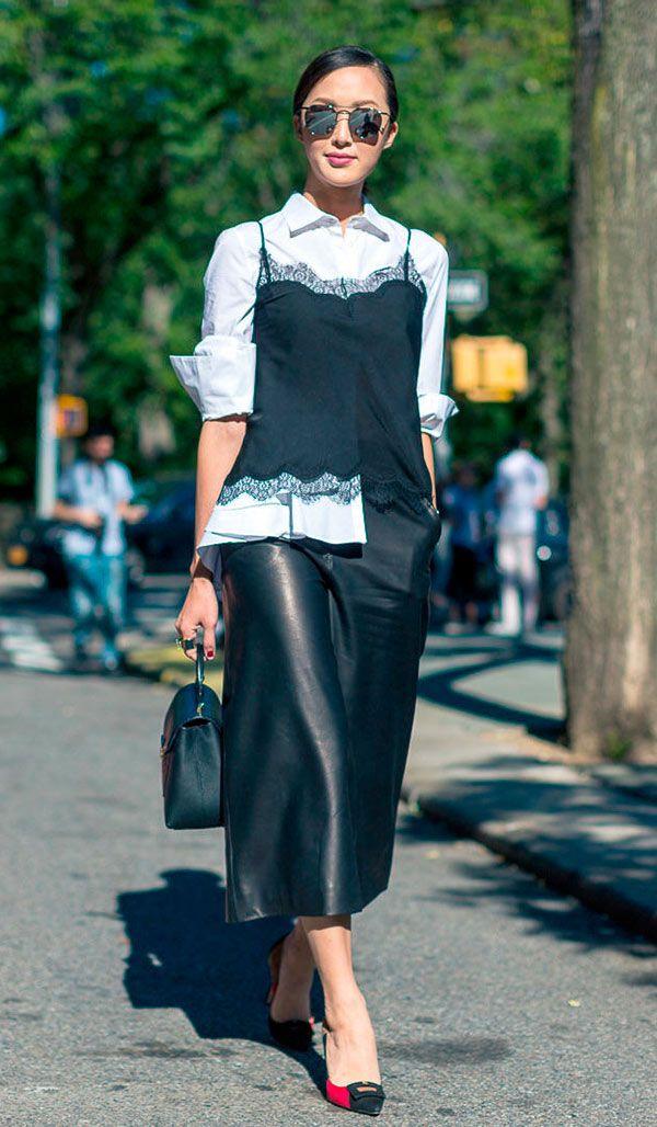Street style look com camisa com top e saia couro midi.