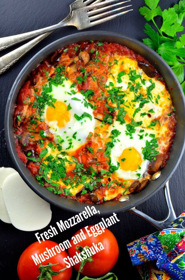 Shakshuka, eggs in spicy tomato sauce with vegetables and creamy fresh mozzarella cheese
