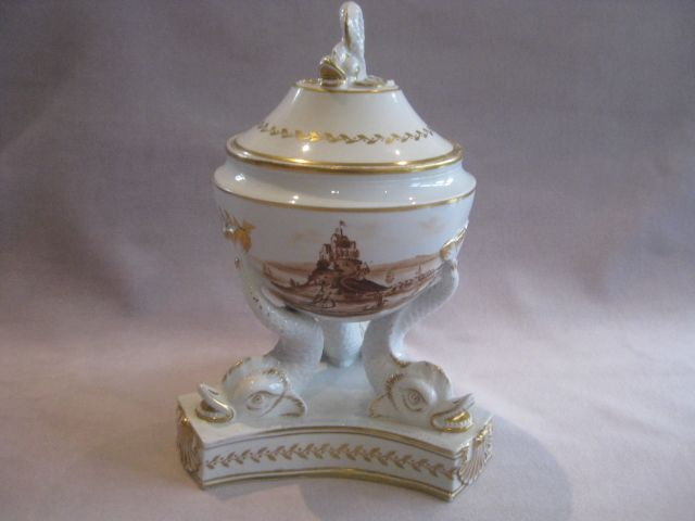 A fine Chamberlain tureen standing on a triform base with three dolphins supporting. The lid with a dolphin finial and the bowl painted in monocrome brown with a coastal scene.  Unmarked  Circa 1820  Height 8""