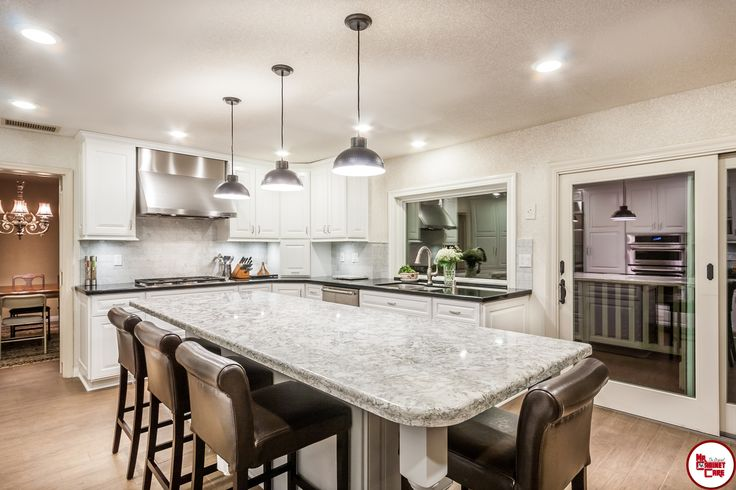 This traditional all white kitchen features a large center island, offering plenty of seating and storage. The stainless steel appliances and lighting elements add a modern feel.  #kitchen #kitchenremodel #whitekitchen
