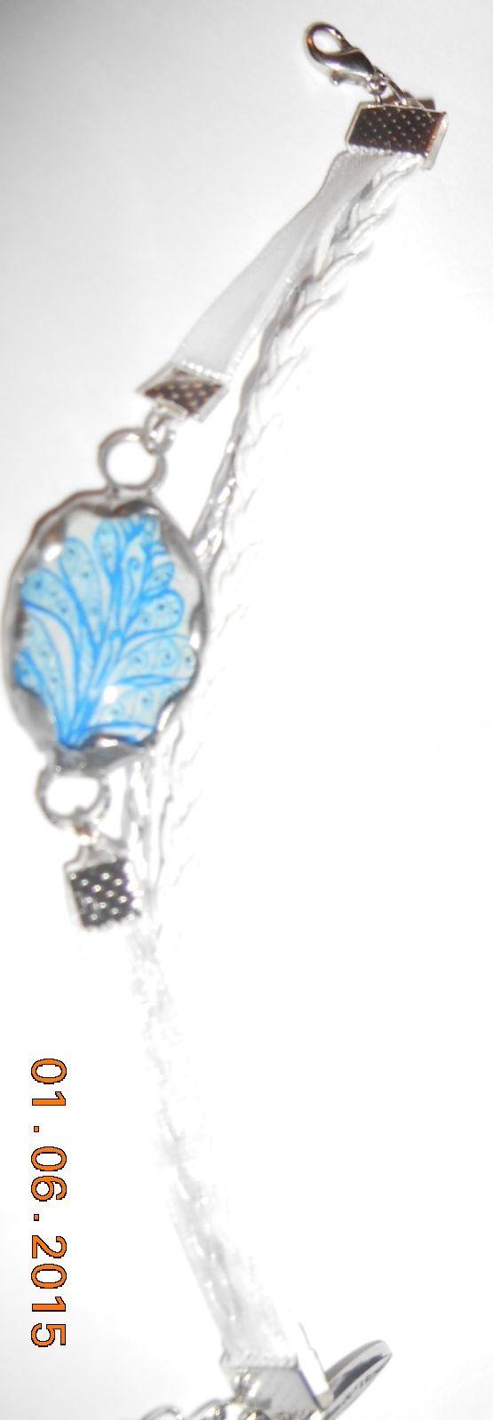 """Bracelet ajustable, cordons et rubans blanc et argent, bille de verre ovale avec dessin de la collection """"Feuille bleue"""", dessiné par JOS, serti d'étain.   artsvitrail@hotmail.com  FB: Arts & Vitrail  VENDU"""