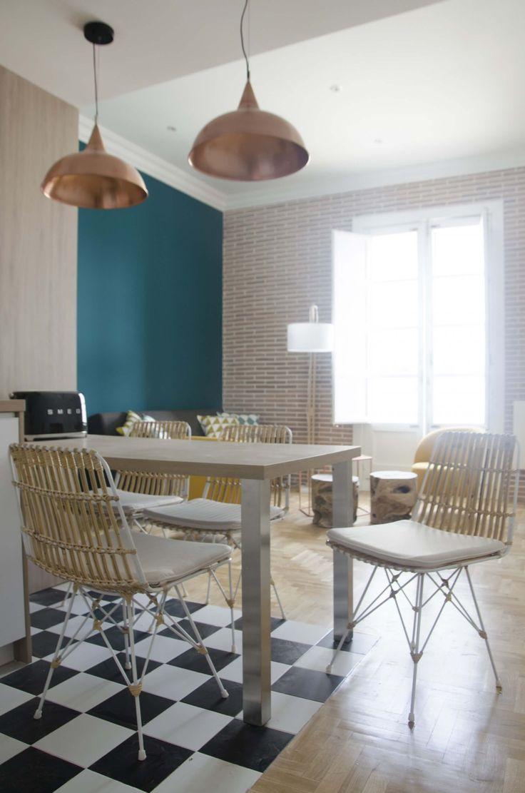 """Cocina """"open concept"""" con suelo de damero blanco y negro. Sillas de ratán y lámparas de cobre. Pared del estar en color azul pato. Proyecto de reforma de R de Room (www.rderoom.es)"""