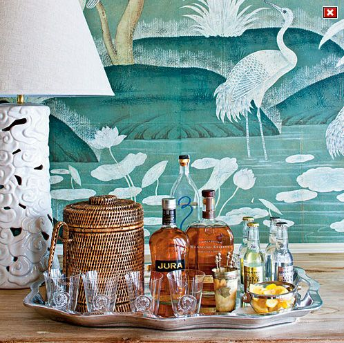 Tabletop bar - Phoebe Howard, Photo by Laurey W. Glenn for Southern Living features silver scalloped serving tray, wicker ice bucket and swan painting to frame the background.