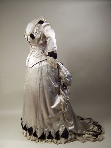 Half-mourning dress by W. G. Jay & Co, 1883-1884, London, via Manchester Art Gallery. Half-mourning dress (?) Pale grey satin trimmed with black figured and black corded silk and white net. Two piece. Bodice lined with cream twilled silk. Low square-cut neck. Fastening at center front with embroidered buttons. Neck trimmed with band and double frill of net. Sleeves shaped to wrist, trimmed with frill of net. Separate skirt lined with stiffened cotton, fastening left back. Hem cut in…