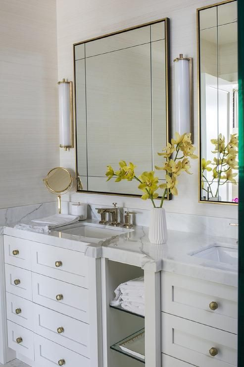 White and gold master bathroom features tan grasscloth on a wall lined with a white dual washstand adorned with brushed brass hexagon knobs  flanking glass towel shelving topped with white marble fitted with his and her sinks and polished nickel faucets.