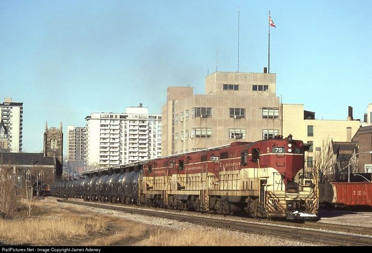 Three GP7s accelerate past TH&B's Hunter Street Station with a unit train of sulfuric acid bound for a fertilizer plant in Port Maitland, Ontario. Hauled from Northern Ontario to Toronto by Canadian Pacific, it then ran as an extra via CN's Oakville Subdivision (over which CP had running rights) to Hamilton, where it was handed off to the TH&B.