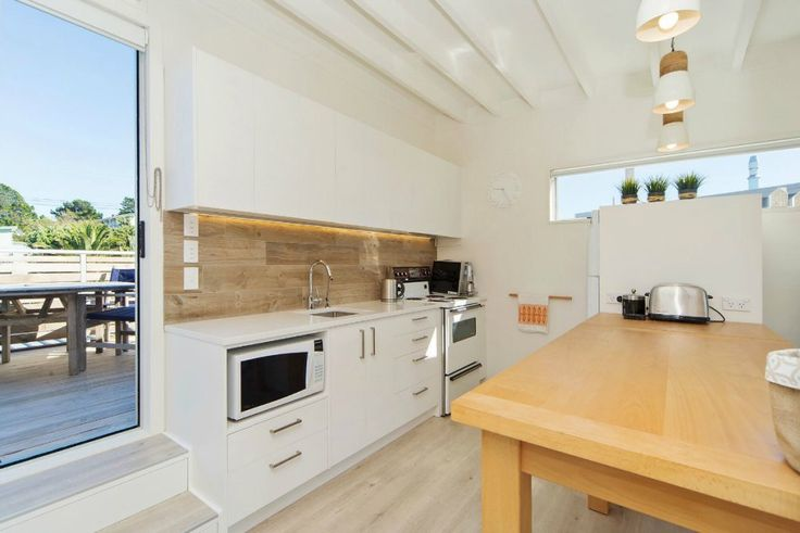 coastal kitchen with timber splashback and white cabinetry on The Life Creative