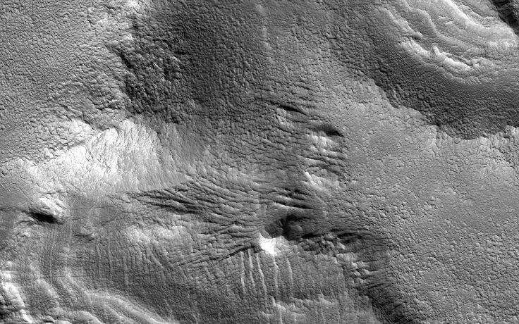 Ice-rich mantling deposits accumulate from the atmosphere in the Martian mid-latitudes in cycles during periods of high obliquity (axial tilt), as recently as several million years ago.    These deposits accumulate over cycles in layers, and here in the southern mid-latitudes, where the deposits have mostly eroded away due to warmer temperatures, small patches of the remnant layered deposits can still be observed.