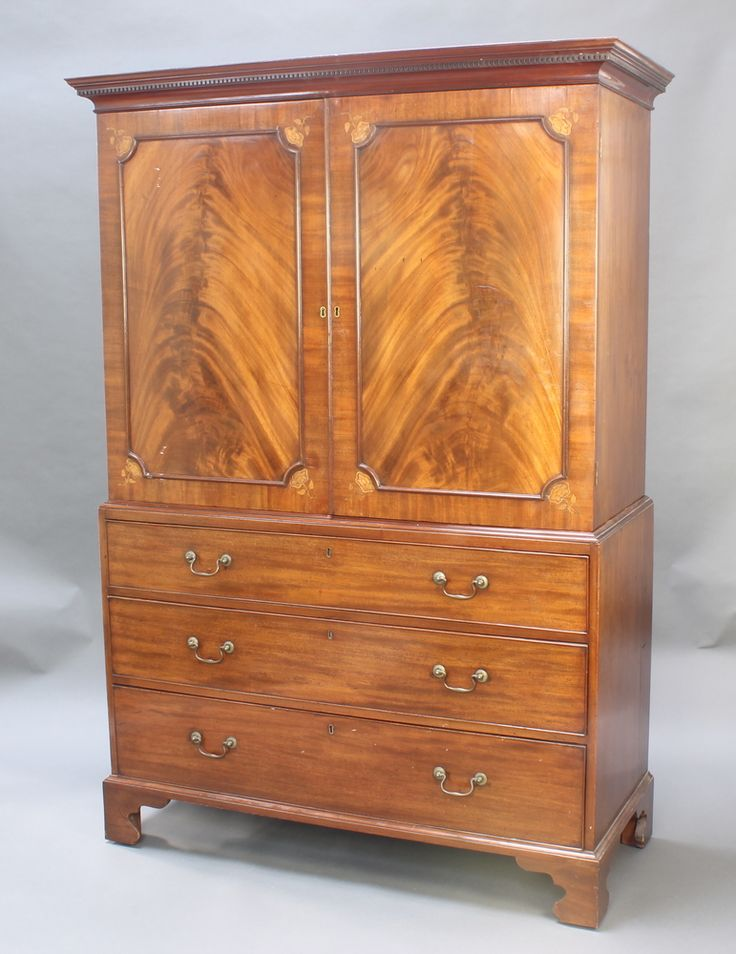 """Lot 926, A 19th Century mahogany linen press with moulded and dentil cornice, the interior fitted 4 shelves enclosed by inlaid panelled doors, the base fitted 3 long drawers raised on bracket feet 72""""h x 50""""w x 21""""d est £200-400"""