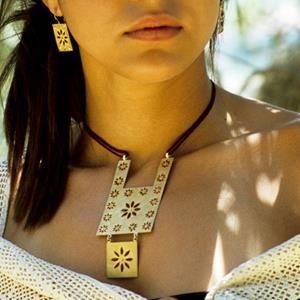 Totemico in oro sabbiato con particolari in rilievo smaltati in rosso. Cordoncino rosso in seta.