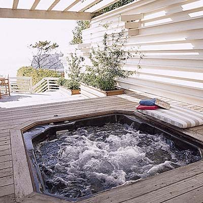 A pre-fabricated acrylic hot tub was sunk 1 1/2 inches below the surface of this Palos Verdes deck, then rimmed it with 6-inch-wide redwood molding so that it appears to float. The hot tub is supported underneath by a concrete slab resting on the ground.