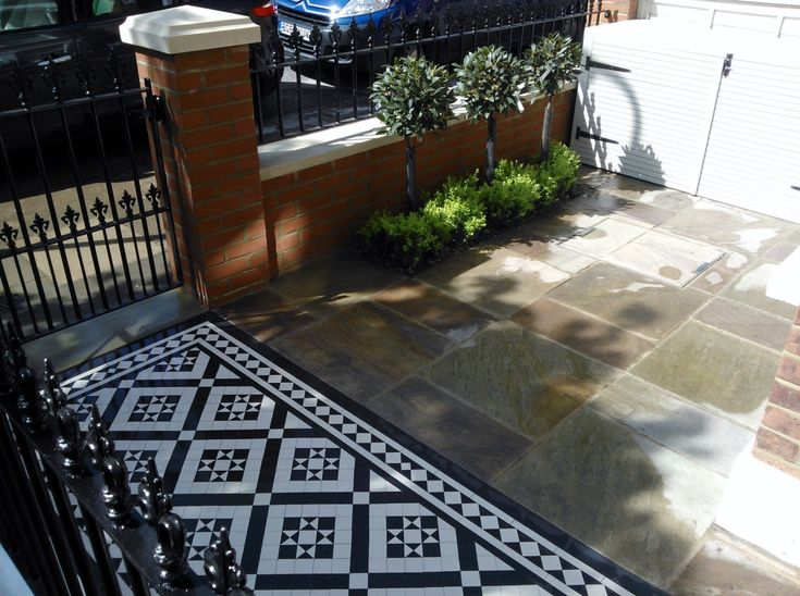 victorian mosaic tile path sandstone paving red brick wall with yorkstone cap bin store and formal planting west london