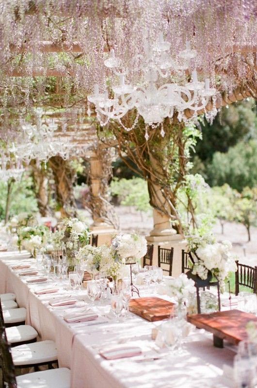 Purple wisteria drips around these gorgeous chandeliers under a pergola.  What a beautiful wedding dinner backdrop.  Click here to see more pics of this gorgeous wedding.