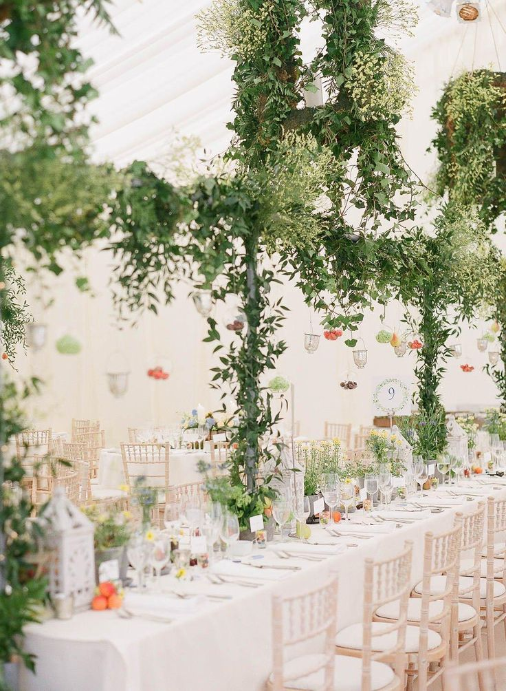 A romantic and ethereal wedding tabletop designed by Laura Lee Flowers, with hanging tea lights from a trellis wrapped in greenery