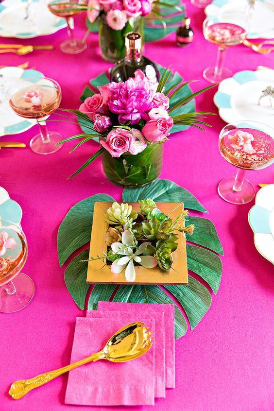 Decoração tropical e colorida para mesa de carnaval com flores, talheres, louças, toalha rosa e vasos de vidro.