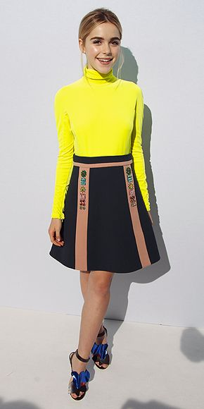 Kiernan Shipka in a bright yellow turtleneck and embellished skirt