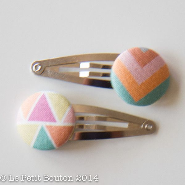 1 pair of 23mm gorgeous designer geo triangle and chevron fabric covered button hair ties set on 50mm snap clips. Button pattern may vary.