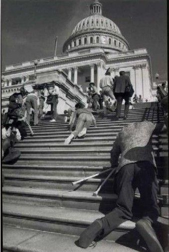 """Disability activists abandon their wheelchairs and mobility devices and crawl up the 83 stone steps of the U.S. Capital Building demanding the passage of the American with Disability Act, March 12, 1990."""