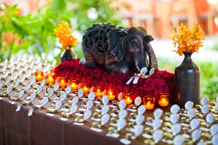 An elephant – the bride's favorite animal – sitting on a bed of crimson roses surrounded by votive candles serves as a striking centerpiece. Photography: Mi Belle Photographers. Read More: http://www.insideweddings.com/weddings/elegant-red-gold-wedding-in-chicago-illinois/366/