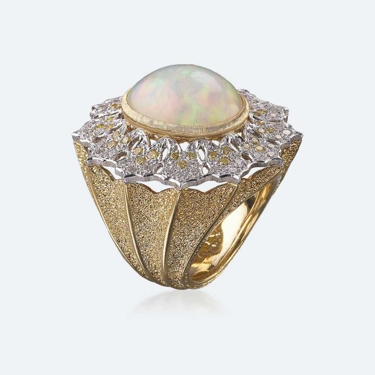Cocktail ring with pale opal set in a white gold bezel, adorned with white and yellow diamonds on a yellow gold band. Stone of the imagination and creativity par excellence, the opal is very much loved for its plays of light deriving from the amount of water it contains, and it is a stone that brings inspiration and strengthens memory. Http://www.facebook.com/diamonddreamfinejewelers http://www.twitter.com/diamond_dream_ http://www.instagram.com/diamonddreamjewelers