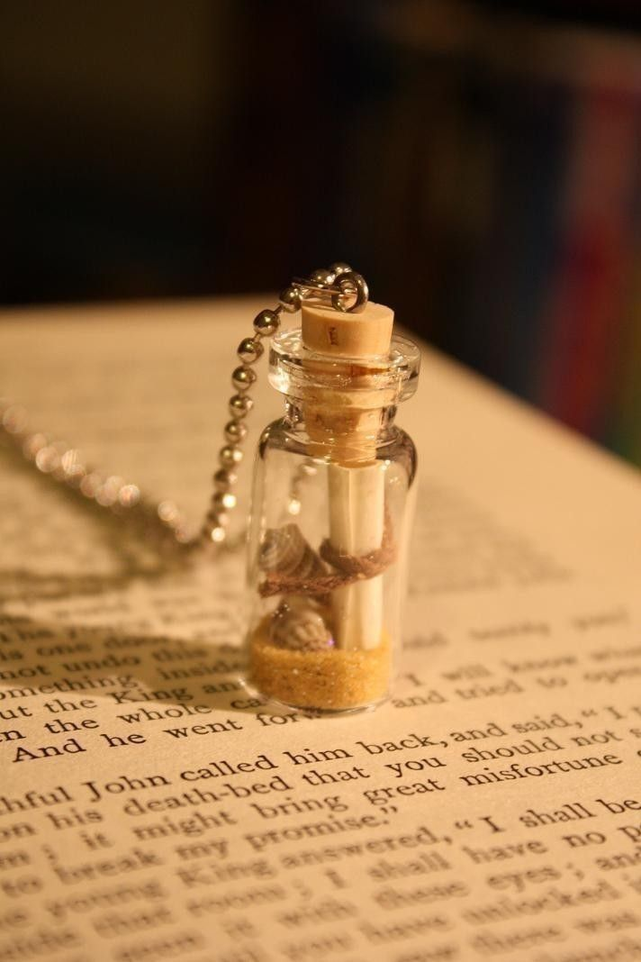 scroll, tiny shells and sand in a small corked bottle