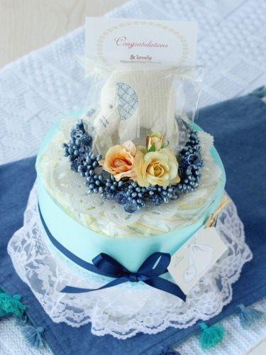 【おむつケーキ】ミニ/1段/ブルー。オムツ10枚にリースと、ビーズラトルをセット。3000円台です。おむつケーキの店アンドラブリー*& Lovelyは、出産祝い、ベビーギフトに最適なオリジナルおむつケーキの通販サイトです。