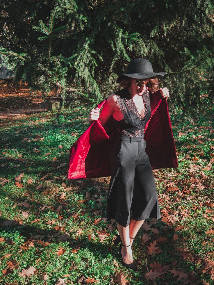 Burgundy waistcoat, lace bodice, wide pants, floppy hat.