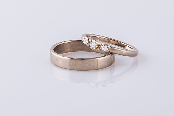 14 karaat witgouden trouwringenset met in de damesring drie diamantjes. De herenring is mat afgewerkt.