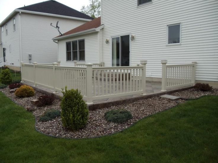 Our vinyl railings and decorative solar lights accent this stamped-concrete patio.