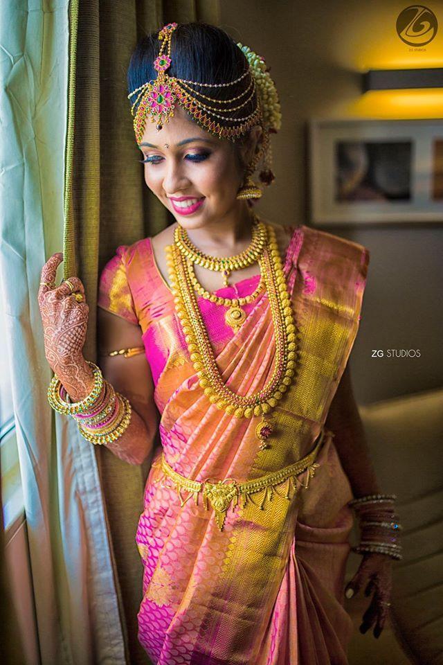 South Indian bride. Gold Temple jewelry. Jhumkis.Pink silk kanchipuram sarees.Braid with fresh flowers.Tamil bride. Telugu bride. Kannada bride. Hindu bride. Malayalee bride.Kerala bride.South Indian wedding.