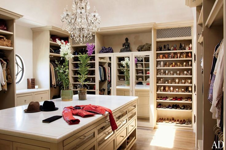 An antique crystal chandelier enlivens Gisele Bündchen's closet, which features custom-made cabinetry and marble countertops.