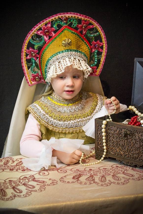 """Russian Princess in Kokoshnik."" A little Russian girl in a stylized traditional attire is choosing some decorations from her jewellery box"