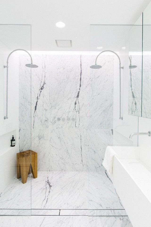 Modern bathroom an open marble shower, and a wooden shower stool