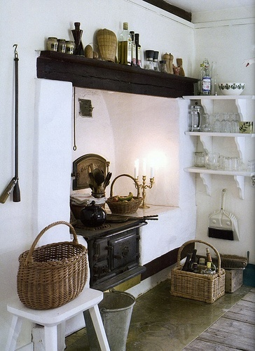 ~I love this country kitchen with its old stove and dark beams, from a Swedish cottage....and great shelves.~