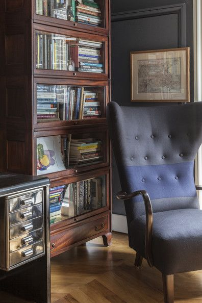 A tufted wingback chair beside a wooden bookcase   Lonny.com