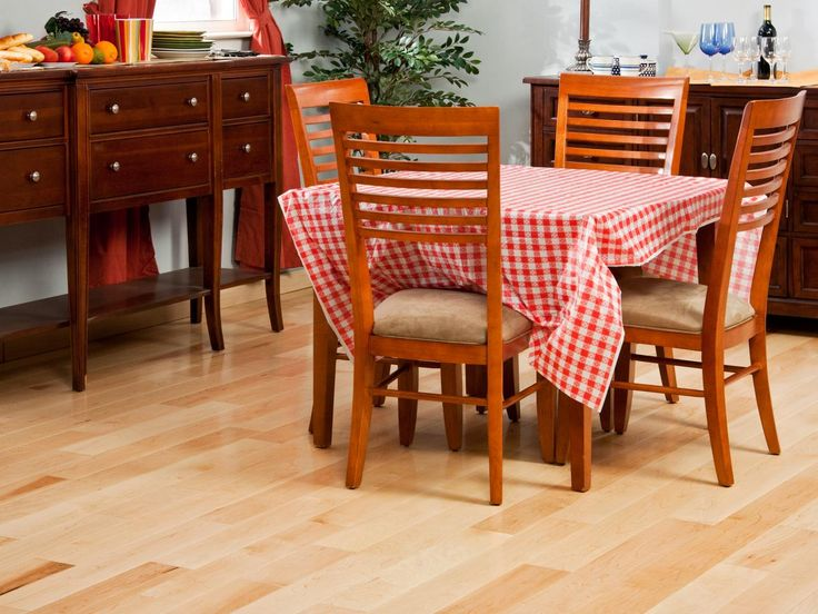 The light hardwood floor brightens up this dining space, even with a dark wood sideboard and server. Adding a small dining table for four and a fun gingham tablecloth gives this room an airy, outdoor feel.
