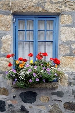 A Stone Cottage with Blue Trim and Window Boxes.