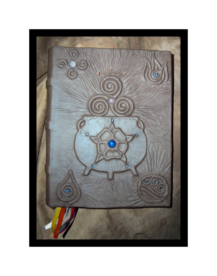 Custom Made - Your Design - Book of Shadows, Grimiore, Spell Book, Book of Mirrors/Journal, handmade, blank  ------  This Custom BOS has their coven symbol as well as each element. Earth is a Leaf with a Star Sapphire, Air is the 4 winds with a Blue Lace Agate, Fire has Blue Sheen Obsidian, Water is ocean waves with Abalone and Spirit is the Cauldron with Lapis. The Desert Rose has 5 petals each tipped by a blue moonstone, the Triskel has a Rose quartz center, and 3 Sunstones represent the…