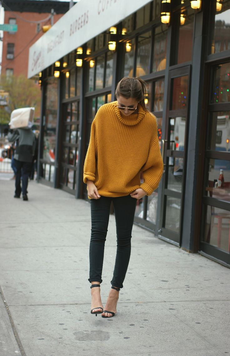 {Oversized mustard knit with ankle-strap heels.}