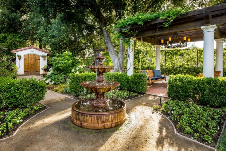Classic white columns pair with rustic wood beams to create a Mediterranean-inspired pergola. An outdoor chandelier hangs above the porch swing and patio area for an intimate, elegant seating area. In the center of the walkways leading through the backyard is a tiered water features that brings soothing ambiance to the space.