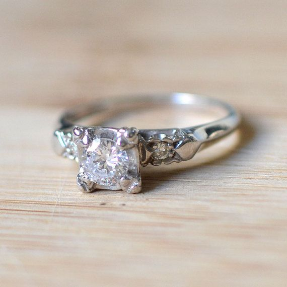 14 karat white gold engagement ring with a center 0.36 carat diamond SI clarity H-I color and two side diamonds at 0.06 carat total weight, circa 1960. Size 5.25.