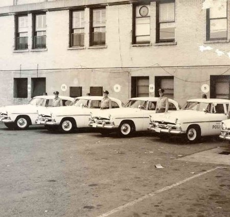 Photo of old police cars in side lot of Municipal Building (1956)