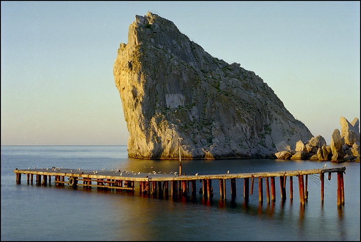 Abandoned wooden pier in front of giant stone. Tags: sea, stones, rocks, pier