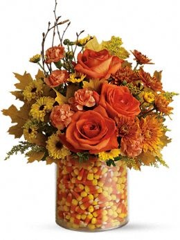 Great for a fall wedding...imagine candy corn and blooms....wow effect!  (make sure the flower stems are placed in a holder inside the candy corn if you are planning on eating it)