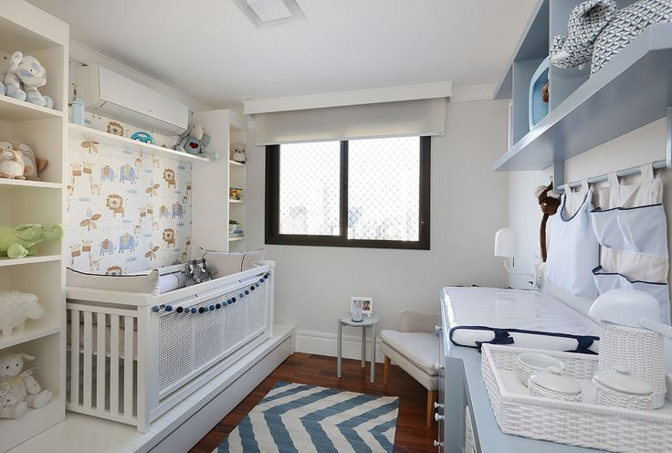 Decoração de apartamento integrado e com crianças. No quarto infantil, quarto de menino, detalhes azuis, nichos azuis com adornos, bichinhos, tapete azul e branco, trocador e berço.