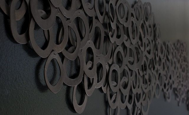 """HALO; Ebb and Flow (detail 1). 42"""" x 102"""" Residential installation. Constructed in black stoneware and fired unglazed to accentuate its natural earthen color and texture. Katherine Dube 2000-2014."""